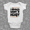 "Unique baby onesies with saying ""I Hooked Daddy's Heart"" in white."