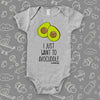 "Grey cute baby onesie with an image of two halves of avocado and saying: ""I just want to avocuddle"""