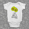 "White cute baby onesie with an image of two halves of avocado and saying: ""I just want to avocuddle""."