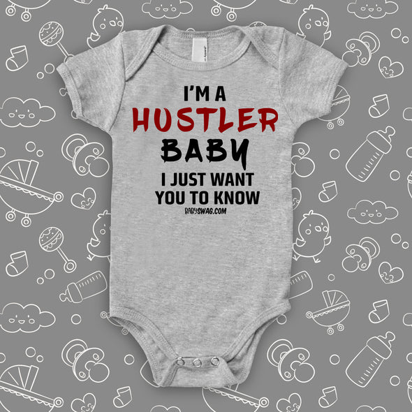 "Funny baby onesies with saying ""I'm A Hustler Baby"" in gery."