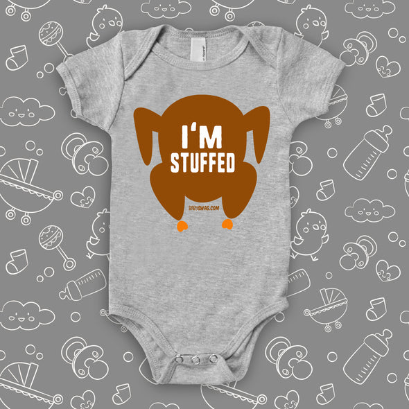 "Hilarious baby onesies with saying ""I'm Stuffed"" and an image of roasted turkey in grey."