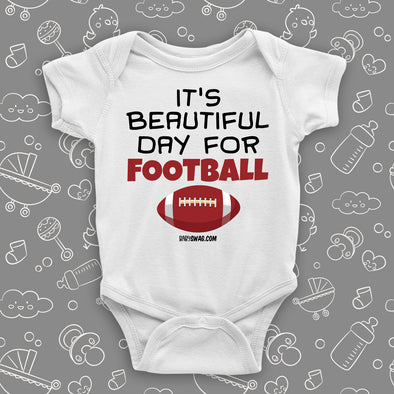 "White baby boy onesie saying ""It's a beautiful day for football"" and a print of a ball."