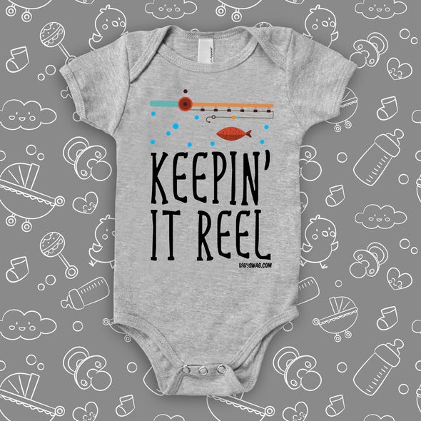 """Keepin' It Reel"" written on a grey cute baby onesie, the drawing of a fishing pole and a fish included."