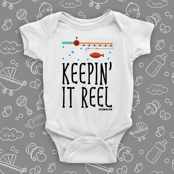 """Keepin' It Reel""  written on a white cute baby onesie, the drawing of a fishing pole and a fish included."