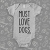"Grey cool baby onesie with print ""Must love dogs."""