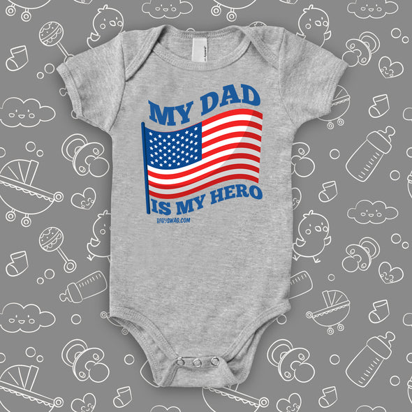 "Grey cool baby onesie saying ""My dad is my hero"" with an image of the American flag."