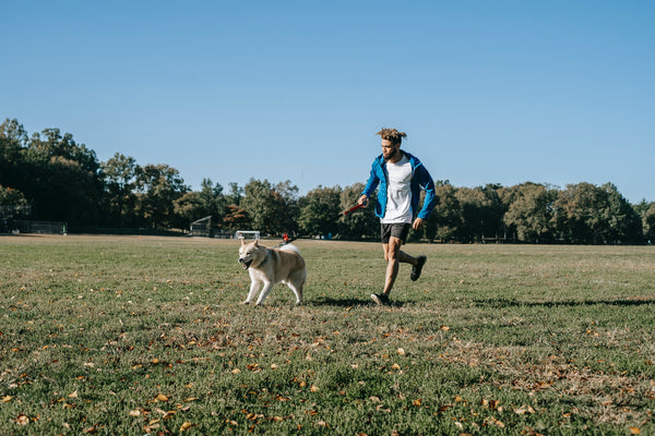 happy dog and owner running in the park.