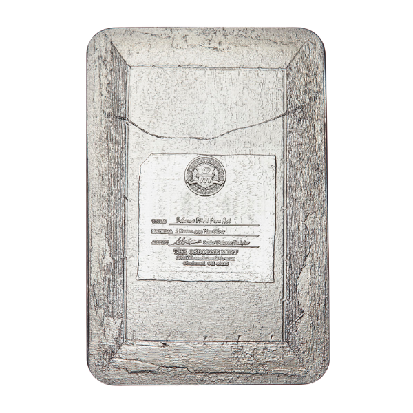 The reverse of this 2 ounce solid silver bar resembles the back of an actual oil on canvas painting with fine details such as a hanging wire and detailed label which features the signatory O/M mintmark.