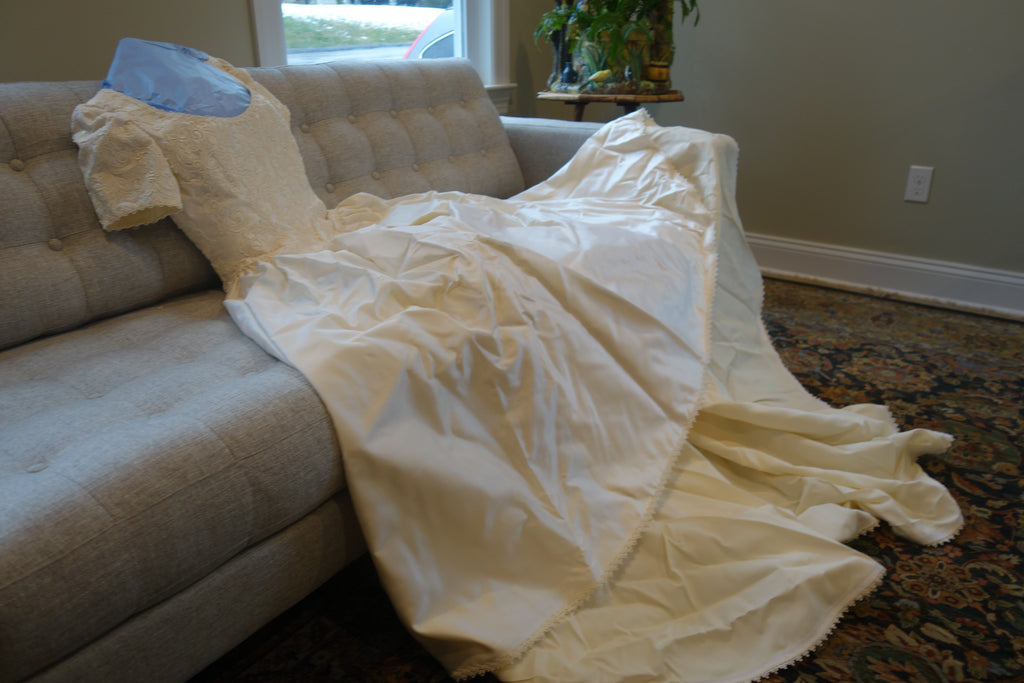 Christos 'Lace' size 4 used wedding dress view of couch