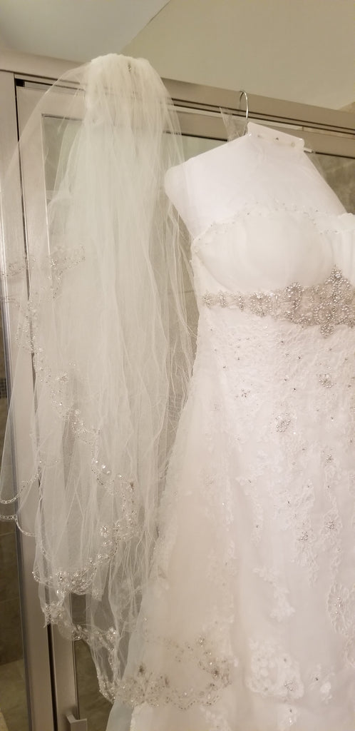 David's Bridal 'Ivory Strapless Organza' size 8 used wedding dress front view close up on hanger