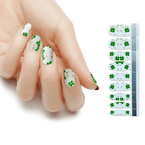 St. Patrick's day manicure with green clovers on white base coat
