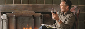 Guest enjoying a glass of wine by the fireplace while reading a book at The Lodge at Torrey Pines