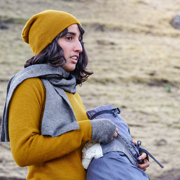 Woman holding a backpack wearing mustard colored baby alpaca wool clothes