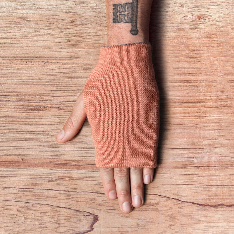 Hand with inside out gloves made of alpaca wool in the color coral