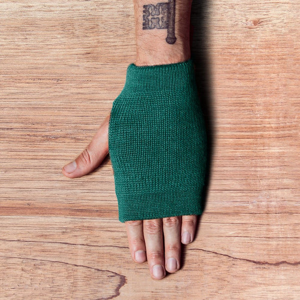 Hand with inside out gloves made of alpaca wool in the color emerald