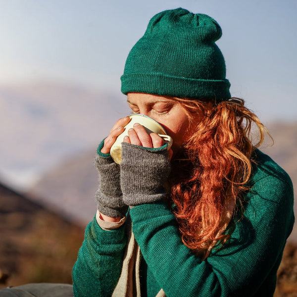 Woman drinking a cup of tea and wearing baby alpaca sweater, beanie, scarf and gloves