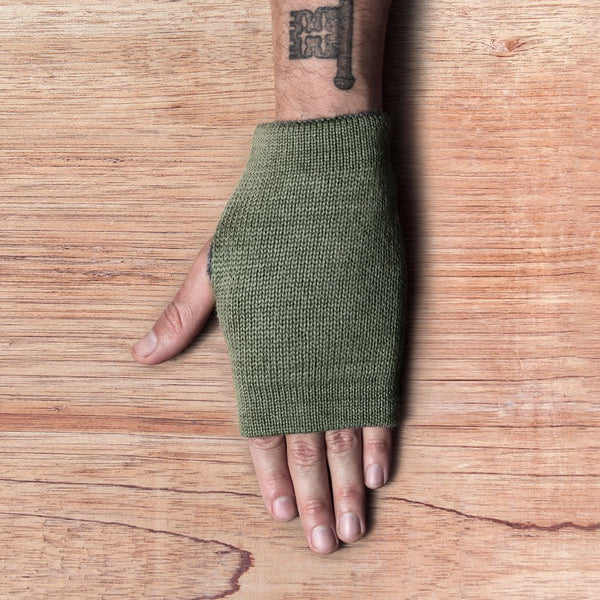 Hand with inside out gloves made of alpaca wool in the color green