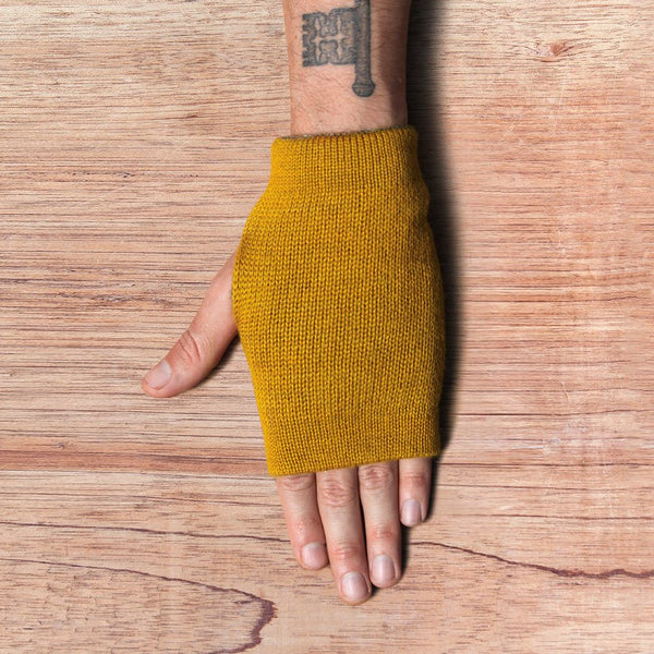 Hand with inside out gloves made of alpaca wool in the color mustard