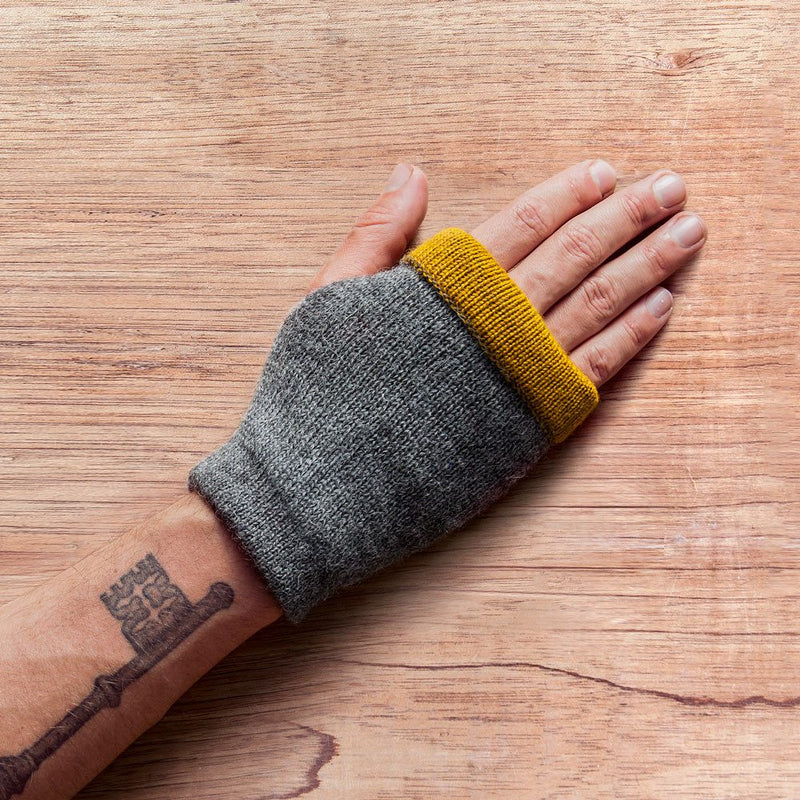 Hand with inside out gloves made of alpaca wool in the color grey
