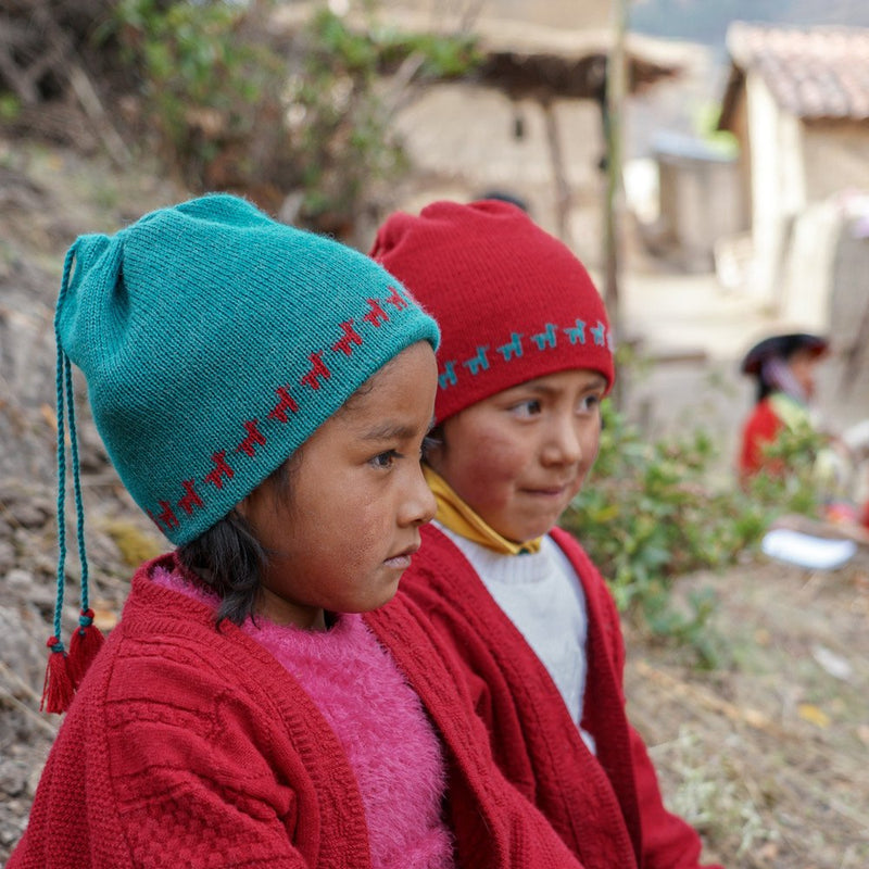 Girls wearing baby alpaca 2 in 1 hat and loop color red and blue