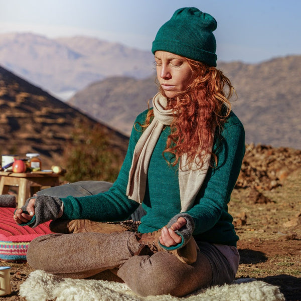 Woman doing yoga with emerald colored baby alpaca sweater, beanie, scarf and gloves