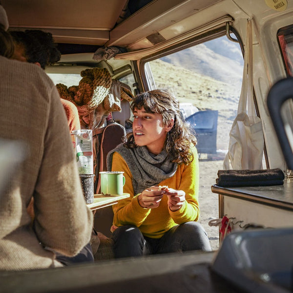 Woman sitting in a camper and wearing mustard colored baby alpaca wool clothes