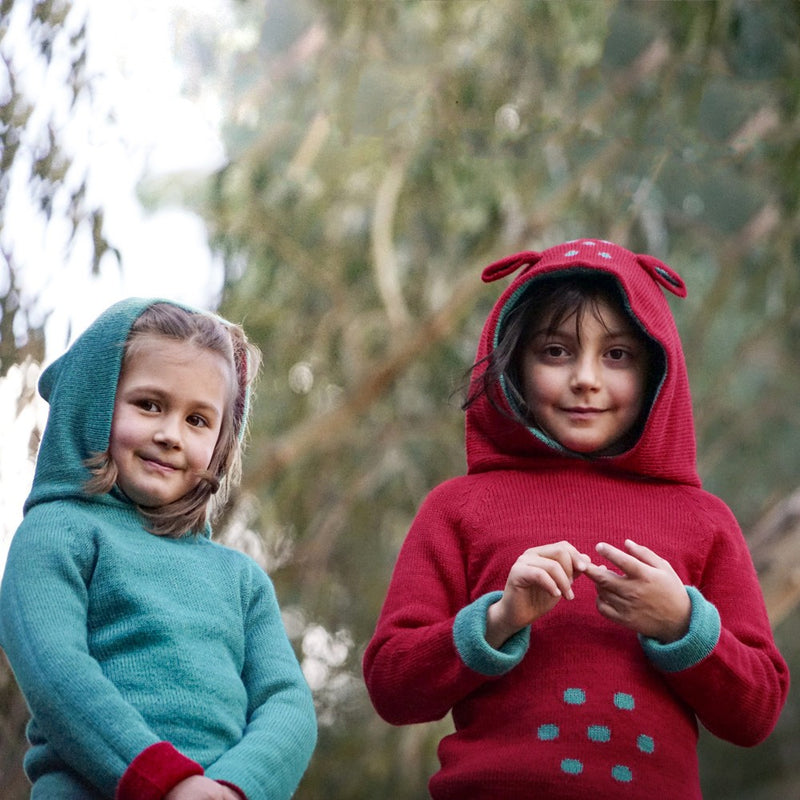 Two girls wearing baby alpaca sweater with hood in the colors blue and red