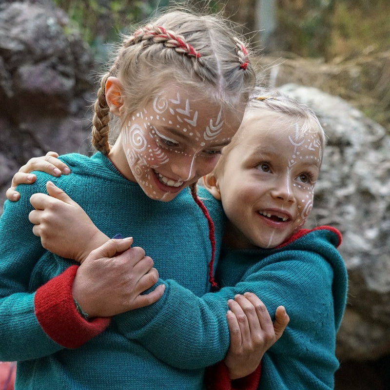 girls hugging each other with painted faces and baby alpaca clothes