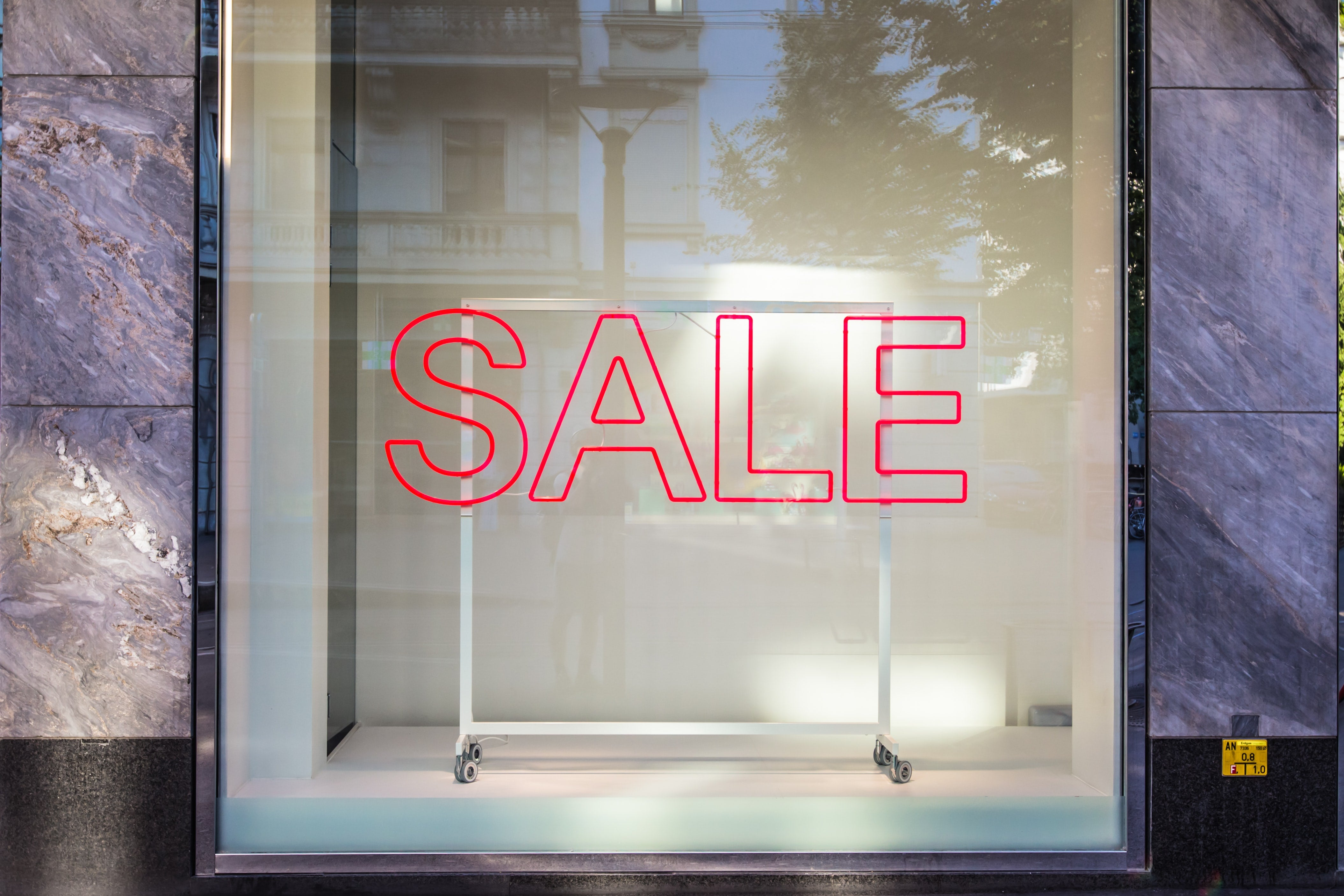 A large SALE neon sign against a window display with an empty clothes rack