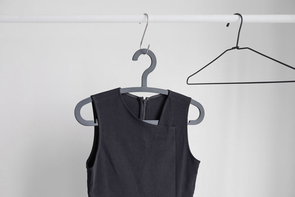 A single black dress hanging on a hanger against a white background