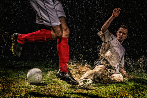 An image of two soccer players playing soccer in the rain at night..