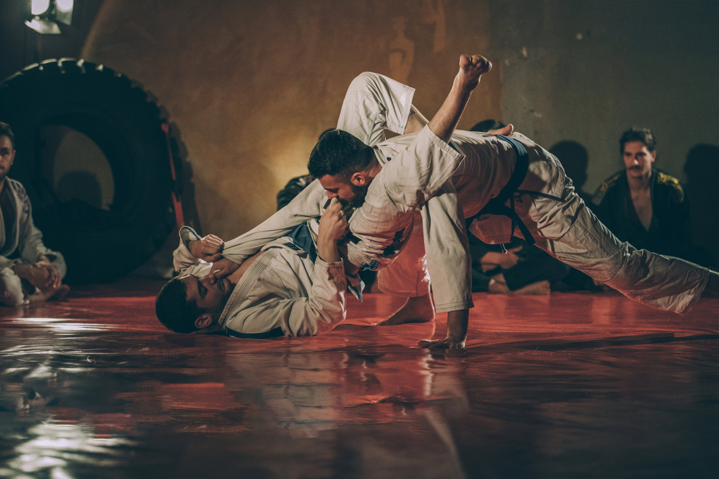 An image of two men practicing jiu jitsu on a red mat.