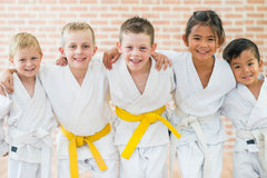 An image of five smiling children in jiu jitsu gis standing together with arms over each others shoulders.