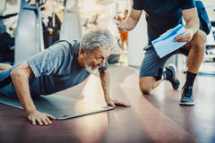An image of a coach and an elderly man doing a push up.