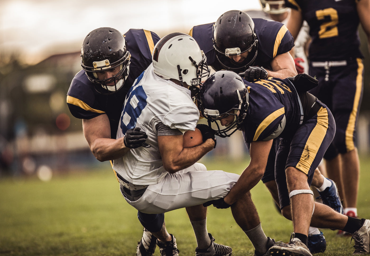 An image of a football player being tackled by three defenders.