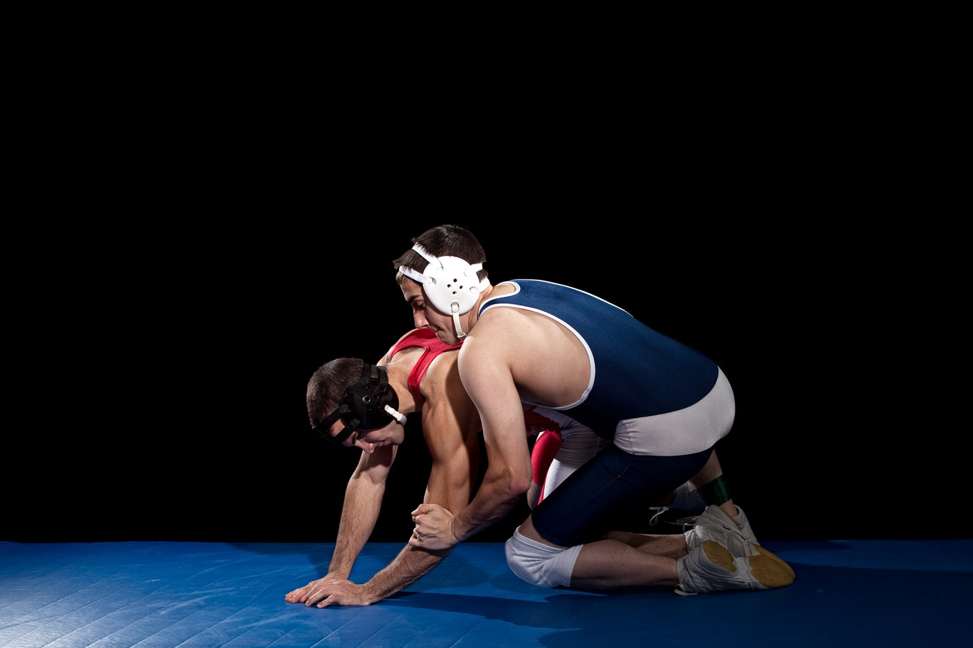 An image of two wrestlers in the referee's position on a blue mat.