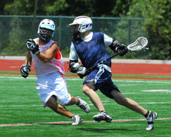 An image of two lacrosse players running on a field
