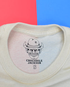 "Label on the inside of the shirt features the outline of the Crocodile Jackson Cowboy logo wearing a hat with the brim flipped up & a bullet hole through the crown. Below is ""Crocodile Jackson"" in a black western font. Below this is the size of the shirt in the same font, but in outline. Photographed is a size small so a capital letter S is shown."