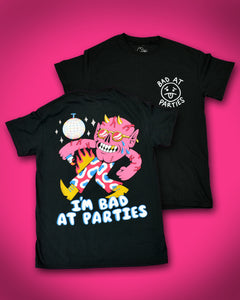Back of short sleeve black t-shirt with a disco ball in the top left corner with a pink dancing monster below it. He has exposed veins, 2 gold horns, 1 gold tooth and gold round sunglasses. He is wearing pink pants with blue cow print outlined with white. He is wearing pointy gold boots and holding a lit lighter in his right hand. Flames are coming from his right pant leg. At the bottom it reads I'm Bad at Parties. Front of shirt has white font that reads Bad at Parties in a circle around a sad face emoji.