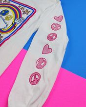 Load image into Gallery viewer, Close-up of shirt's sleeve. Descending down the sleeve vertically are drawings of a heart, the world, a peace sign, and this pattern repeats once more. The designs are all hot pink.