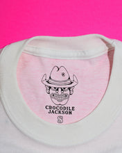 "Load image into Gallery viewer, Close-up of this shirt's tag: the Crocodile Jackson cowboy logo, the words ""Crocodile Jackson"" in a western font below, and an outlined letter indicating size (in this case, the outline of an ""S"" for a size small shirt)."
