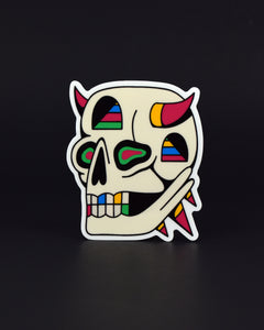 Vinyl sticker of a skull with color-blocked hot pink and yellow horns rising from the temples, an entry way with colorful stairs in the third eye's location, a very long nasal opening, irregularly-shaped eye sockets with seafoam green and hot pink shapes within, a mouth full of teeth that include a pink, blue, yellow, and green tooth in each color, a similar entry way with colorful stairs within located below the horn on the right side, and 3 triangular protrusions from the occipital bone.