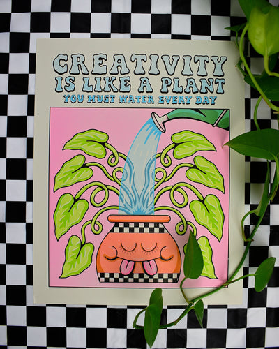 A print of a cartoon plant being watered. The pot has a smiling face with closed eyes and two tongues sticking out. Above the plant is reads Creativity Is Like a Plant You Must Water Every Day in blue font.
