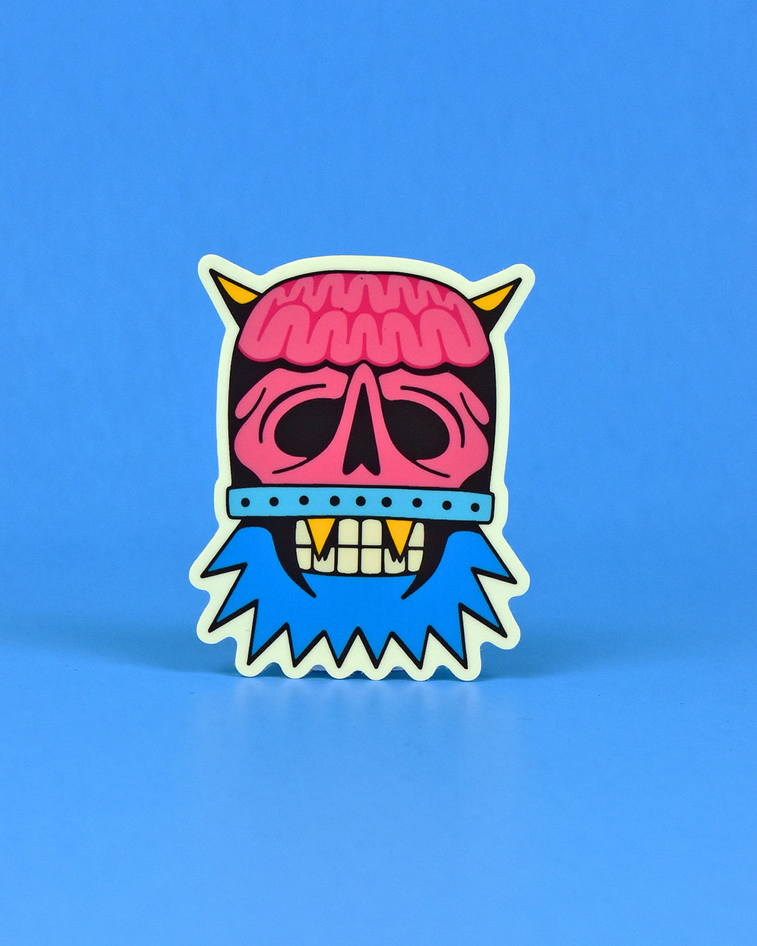 Vinyl sticker of DomeHead, featuring half their face a pink skull and exposed brain encapsulated in a clear dome that is secured with a metal band above the lip, and the other half a blue-bearded, teeth clenched face with 2 gold k-9 teeth. Eye sockets and nasal opening of skull half are hollow. Yellow horns protrude from the top of the dome.