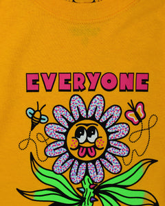 Gold short sleeve t-shirt that reads Everyone is Cute (except for you) in pink font. The (except for you) is in a very small font. In the center is a large flower with a thorny green stalk and 6 flailing leaves. The flower petals are blue, pink and white confetti and the yellow center of the flower has googly eyes round cheeks and a pink double tongue sticking out. On either side of the top of the flower is a flying bee and butterfly.