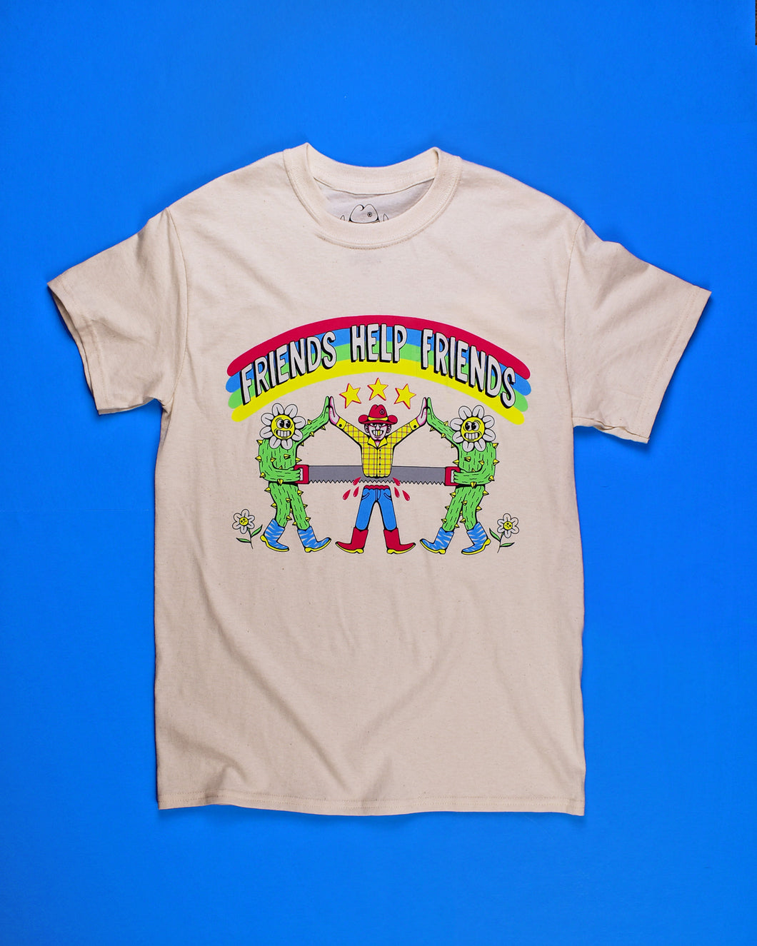 Natural color short sleeve t-shirt with rainbow arch at the top of the graphic with Friends Help Friends on top of it. Two human/cactus with flowers for heads and blue and white zebra print boots on either side of the Cowboy that's in the center. The cowboy has a hot pink hat and boots, yellow plaid shirt and blue jeans. 3 gold stars above the Cowboy. All 3 characters are high fiving each other. The Cowboy is being sawed in half. 2 white flowers at the heals of the human cactus.