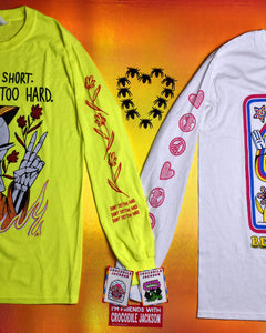 Two t-shirts partly shown with the long sleeves touching as if the shirts are holding hands.  Between the shoulders of the shirts are toy spiders lined up in the shape of a heart.  The cuffs of the shirts have 2 enamel pins on them and a red rectangle sticker that reads I'm Friends with Crocodile Jackson.