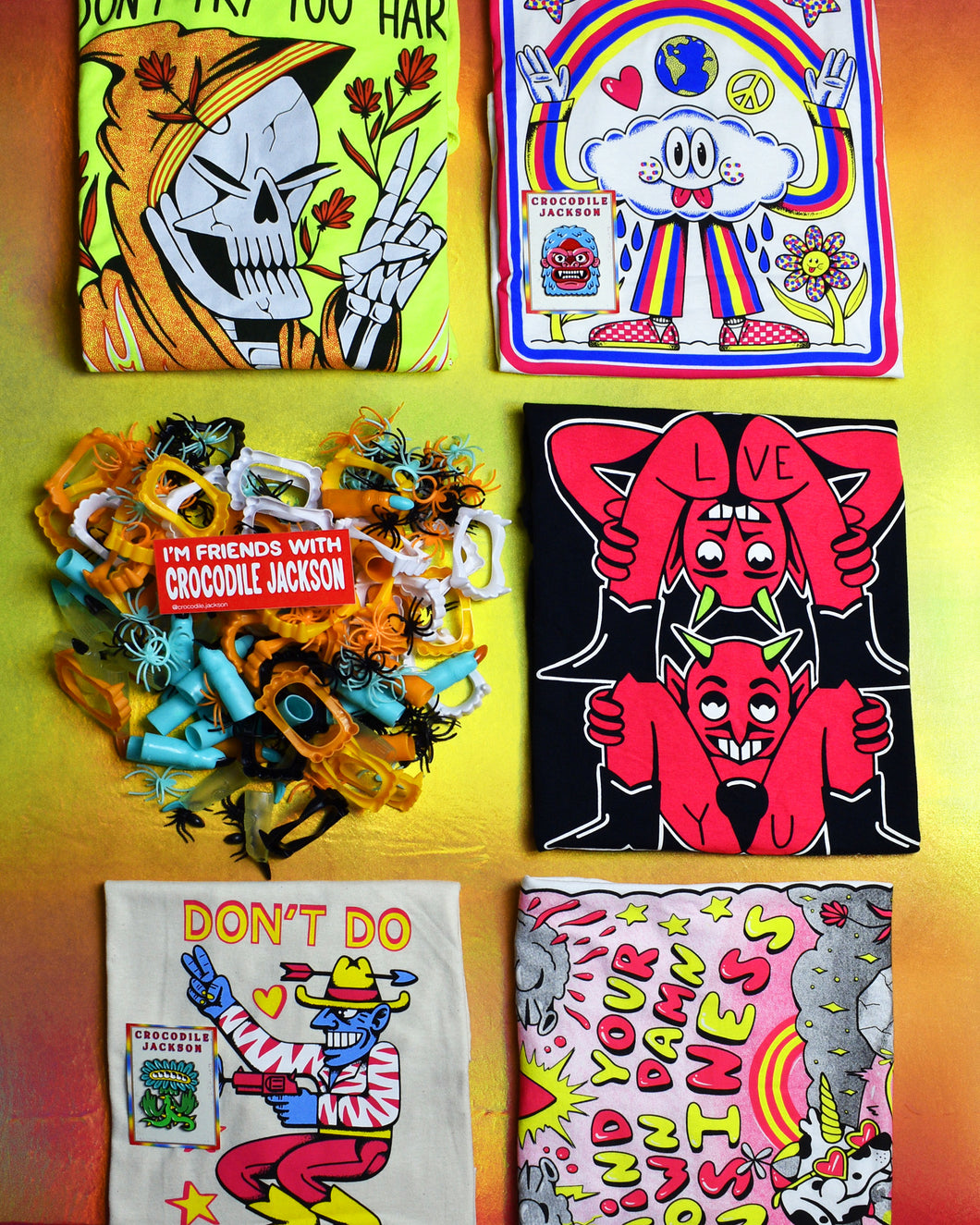 Five various folded t-shirts displayed in a grid format on a orange, gold and pink foil background.  A pile of Halloween toys in the shape of a heart in the left center grid section with a red rectangle sticker on tope of it that reads I'm Friends with Crocodile Jackson.