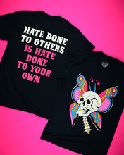Cargar imagen en el visor de la galería, A short sleeve black t-shirt with a white skull plus neck vertebrae. The skull has one gold tooth. Behind the skull are butterfly wings and antennas. The colors on the wings are pink, red, gold and blue. Back of a black short sleeve t-shirt that reads Hate Done To Others in white letters then Is Hate Done To Your Own in hot pink letters.