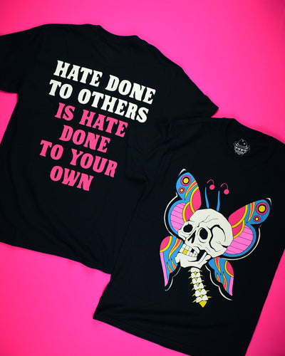 A short sleeve black t-shirt with a white skull plus neck vertebrae. The skull has one gold tooth. Behind the skull are butterfly wings and antennas. The colors on the wings are pink, red, gold and blue. Back of a black short sleeve t-shirt that reads Hate Done To Others in white letters then Is Hate Done To Your Own in hot pink letters.